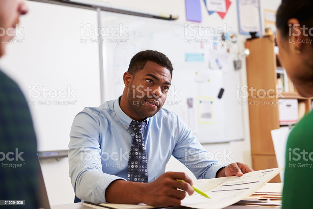 Serious teacher at desk talking to adult education students stock photo