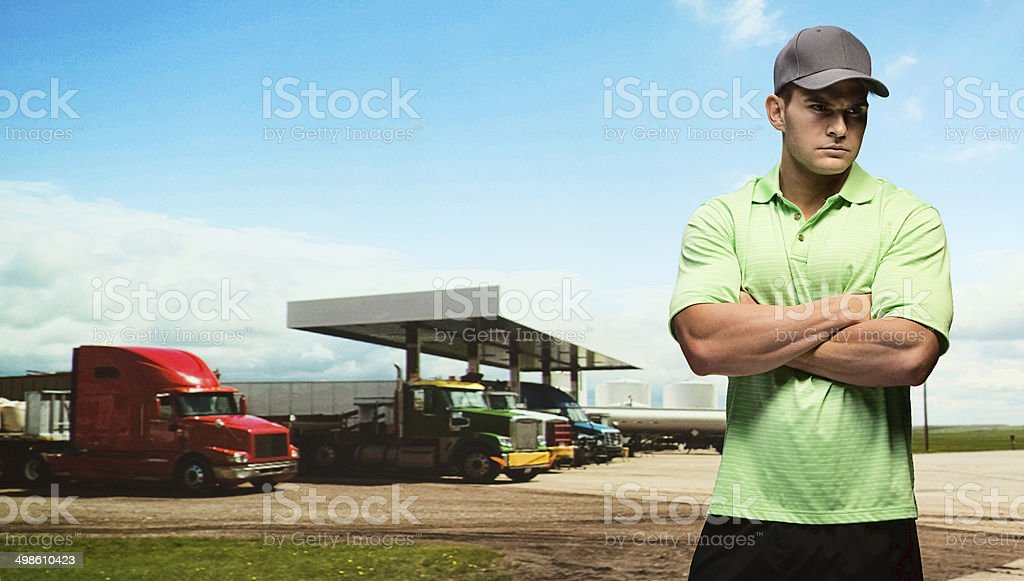 Serious truck driver at the petrol/gas station stock photo