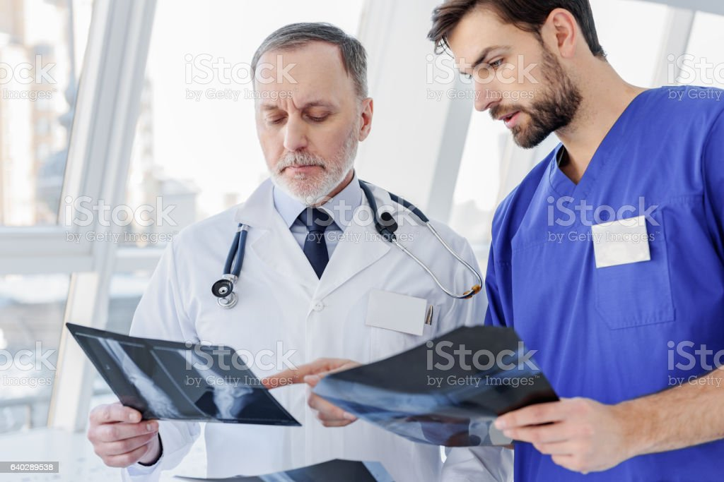 Serious two general practitioners discussing x-ray picture stock photo