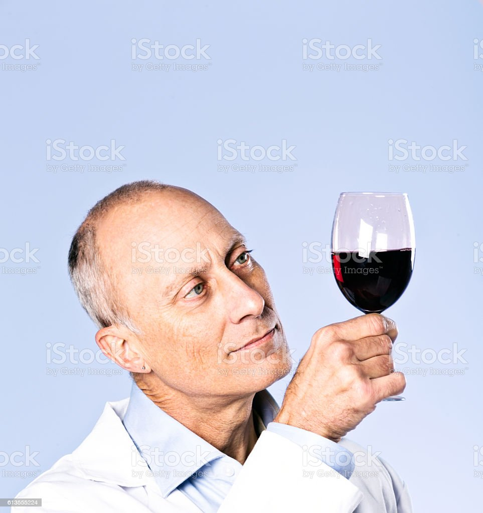 Serious wine-tasting scientist checks clarity and colour of red wine stock photo