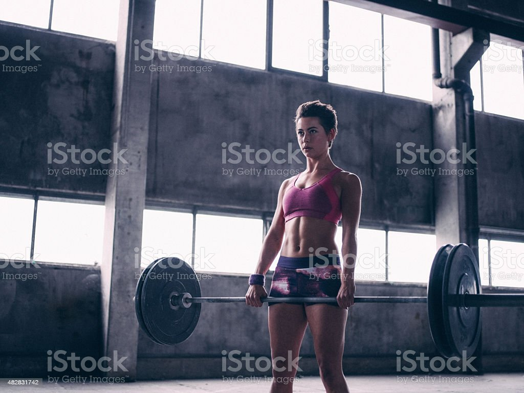 Serious woman holding a barbell with heavy weights stock photo
