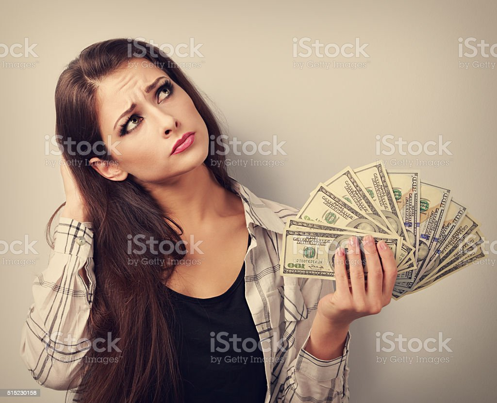 Serious woman holding dollars, looking up and thinking stock photo