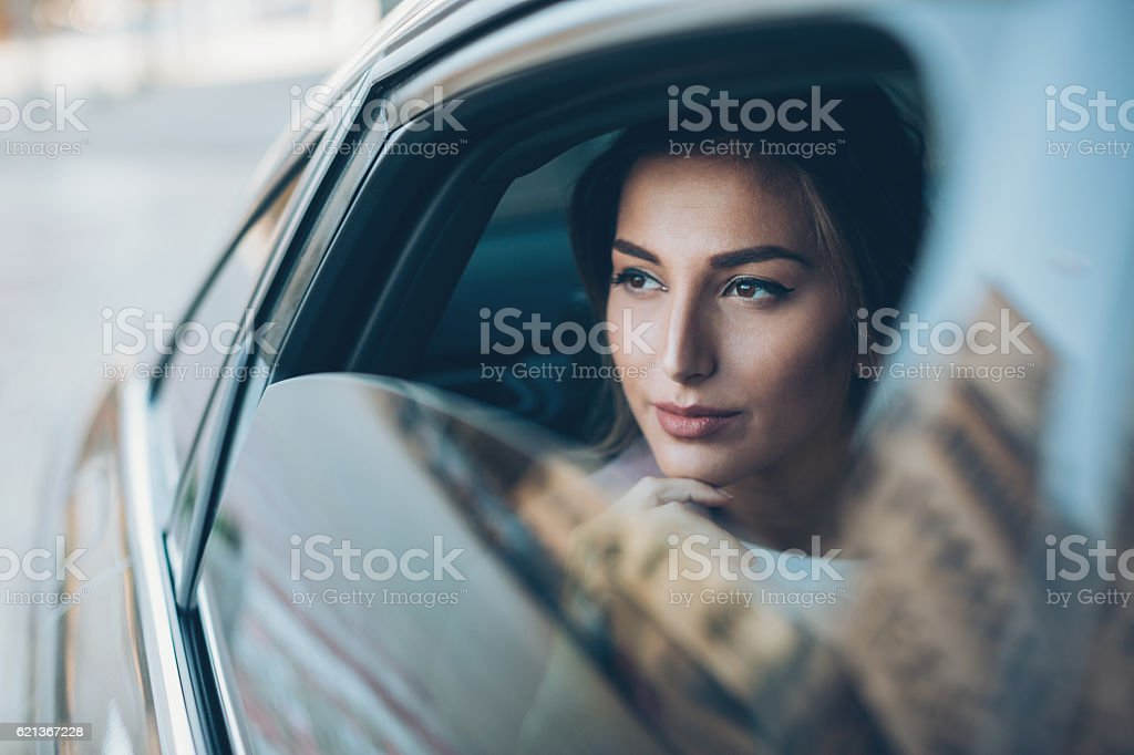 Serious woman looking out of a car window stock photo