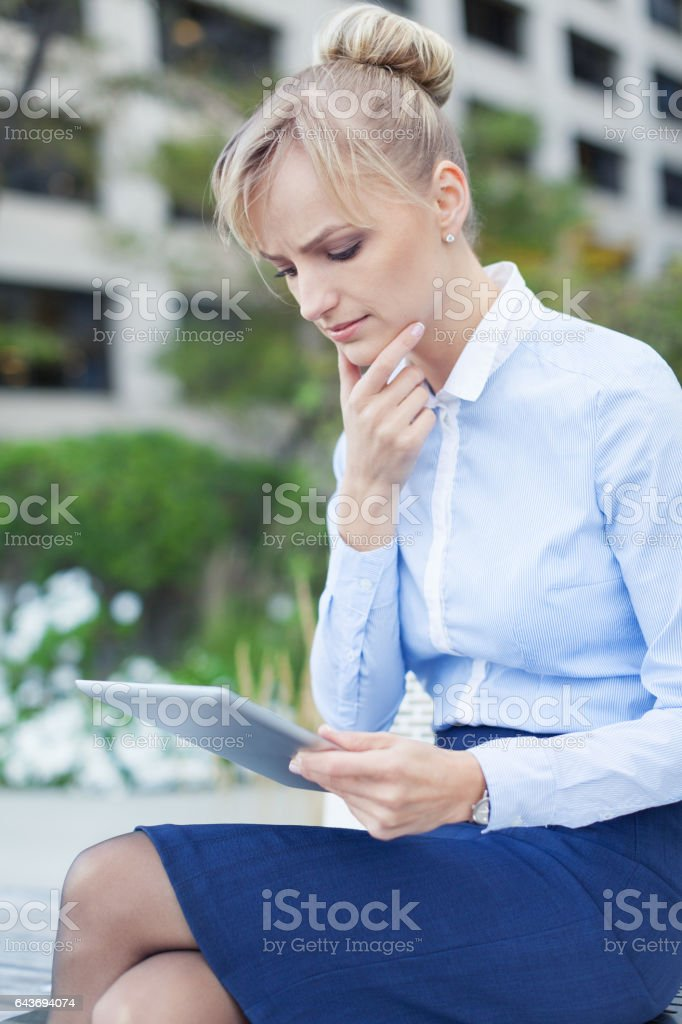 Serious woman reading info on digital tablet with pensive concentration stock photo