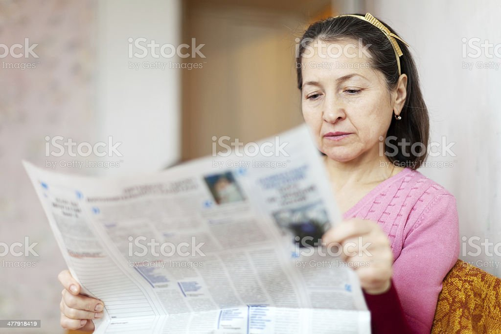 serious woman reading newspaper royalty-free stock photo