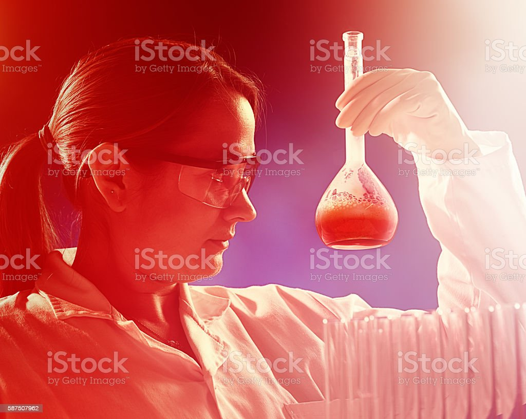 Serious woman scientist studies flask of liquid in red-toned image stock photo