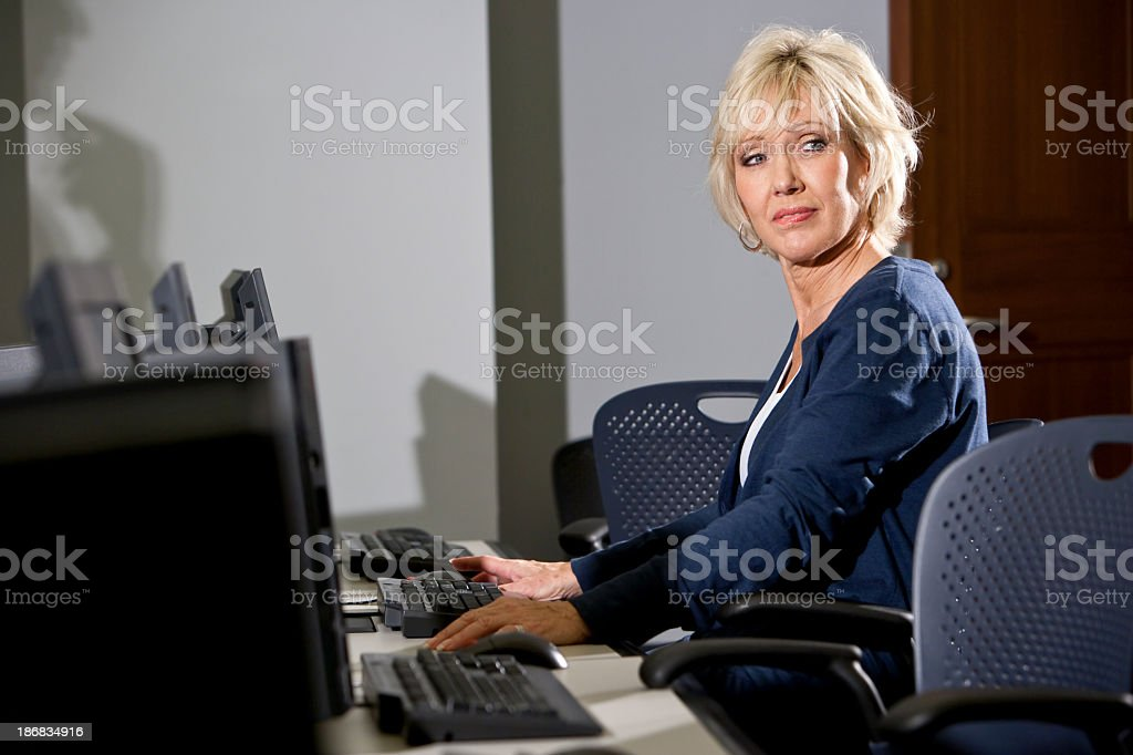 Serious woman using desktop PC in computer lab stock photo