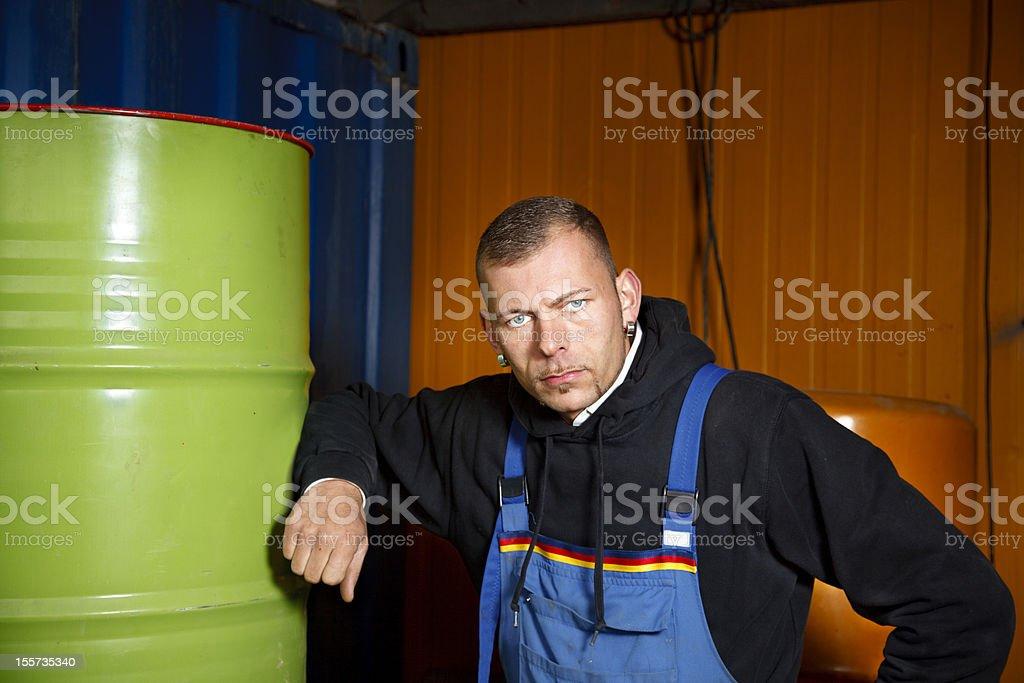 Serious Worker Between Oil Barrels stock photo