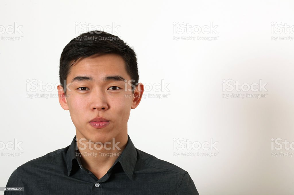 Serious young Asian man looking at camera stock photo