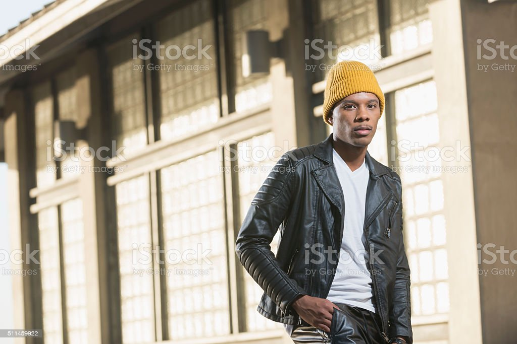 Serious young black man in city wearing yellow beanie stock photo
