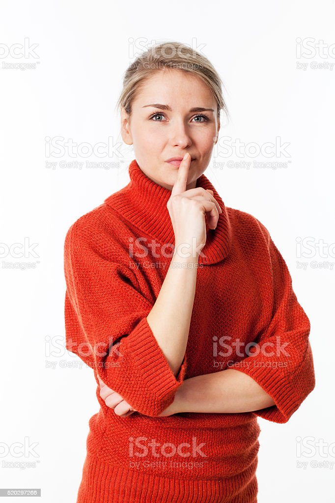 serious young blond woman with index on lips for imagination stock photo