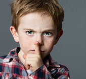 serious young boy asking for silence with finger on lips
