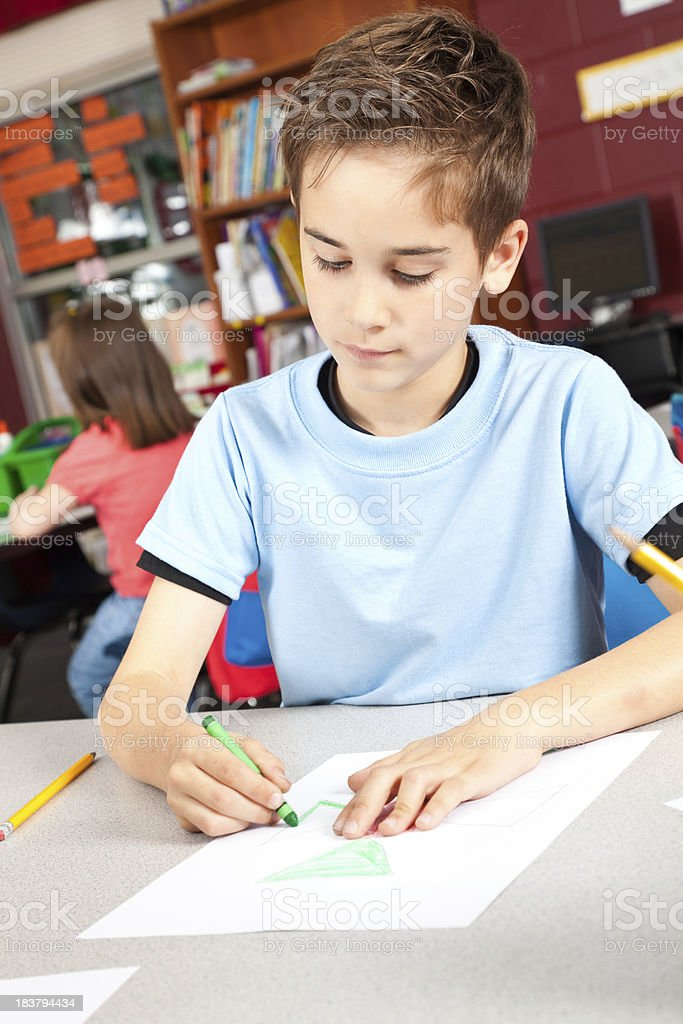 Serious Young Boy Coloring During Class royalty-free stock photo