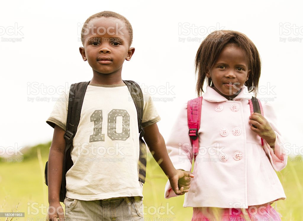 Serious young brother and sister holding hands stock photo