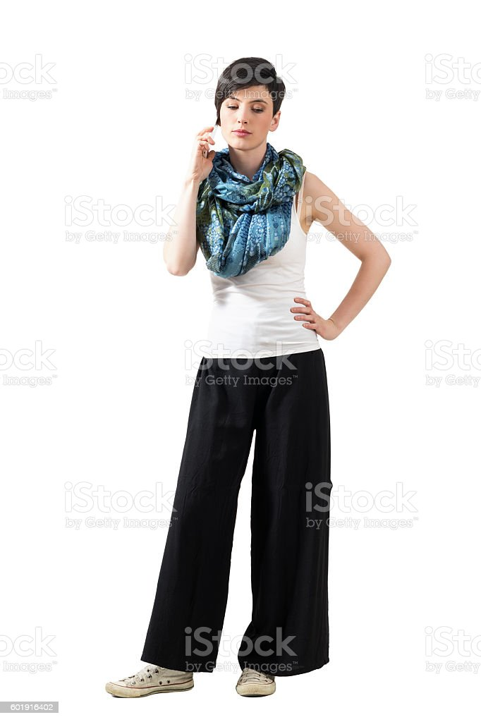 Serious young brunette talking on the cell phone looking down stock photo