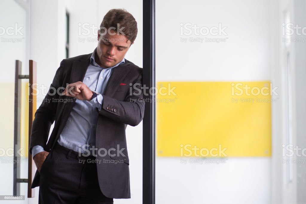 Serious young businessman looking at his watch stock photo