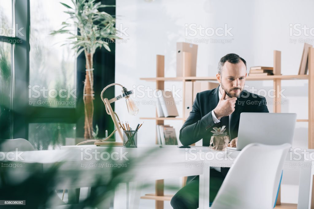 serious young businessman looking at laptop screen stock photo