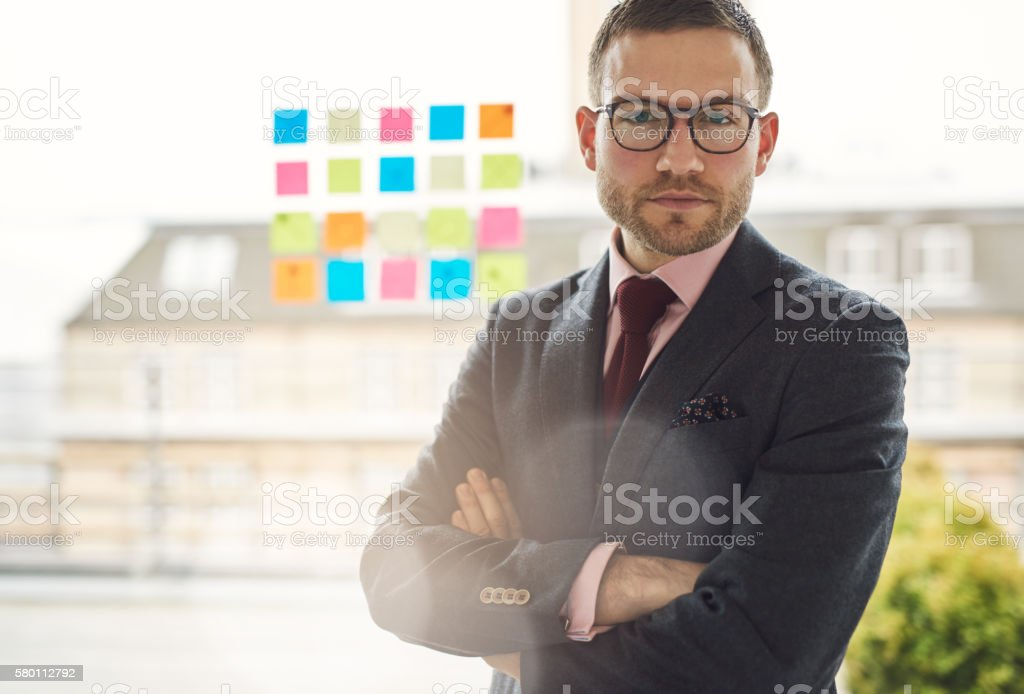 Serious young businessman with crossed arms stock photo