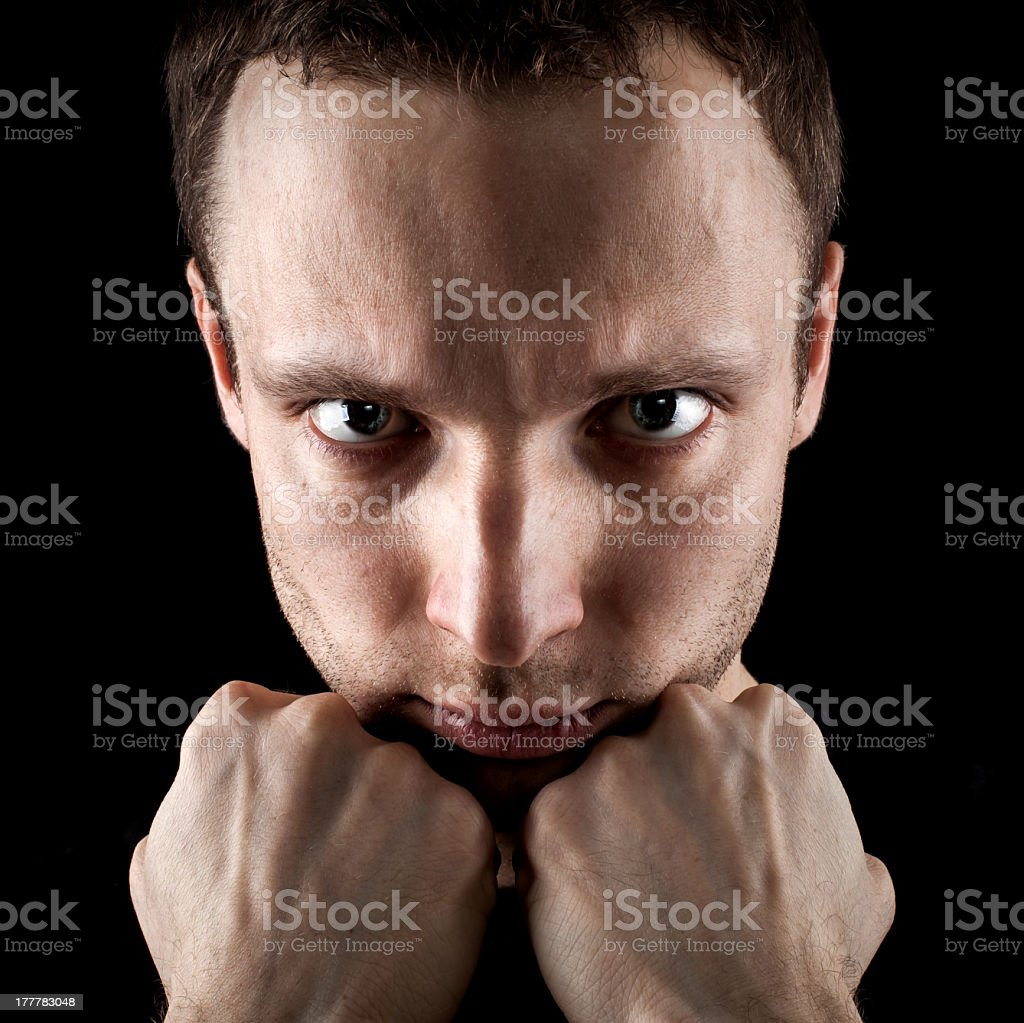Serious young Caucasian man's portrait with fists on black background royalty-free stock photo