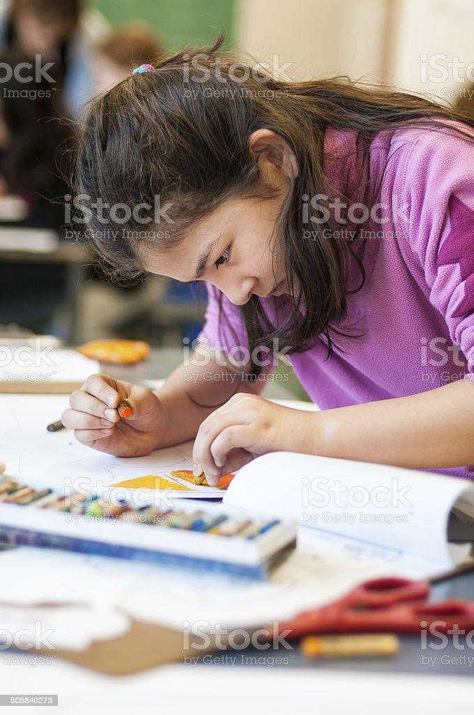 Serious Young Eurasian Girl Drawing in Art Class stock photo
