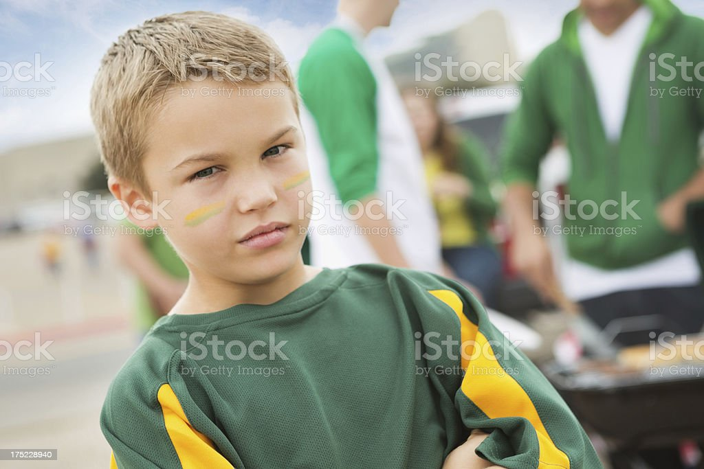 Serious young football fan at tailgate party with family royalty-free stock photo