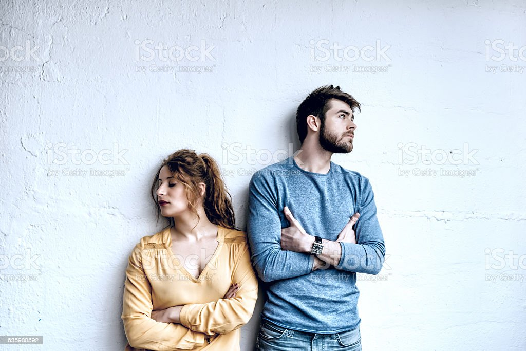 serious young french couple looking pensive in opposite directions stock photo