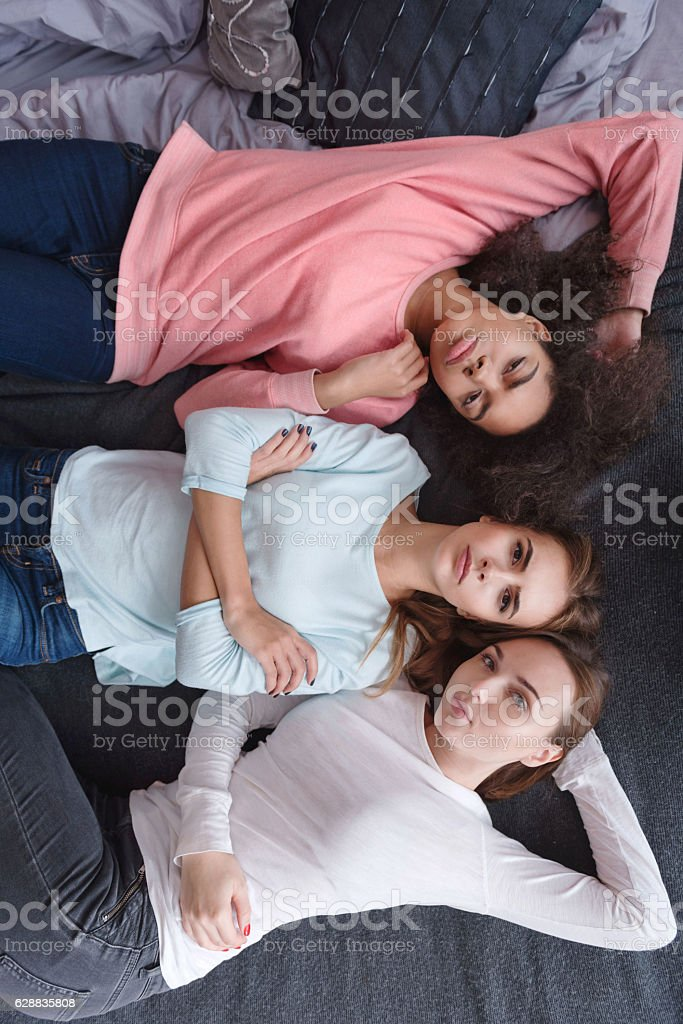 Serious young girls lying on the bed in the bedroom stock photo