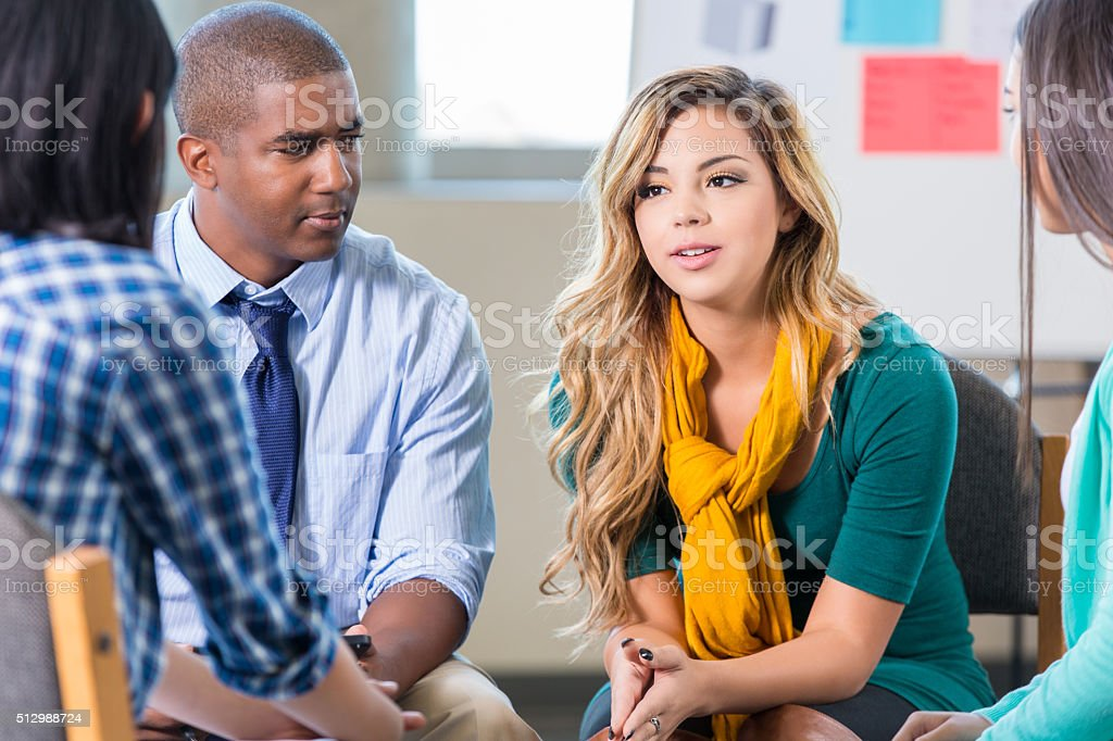 Serious young Hispanic woman in group therapy stock photo