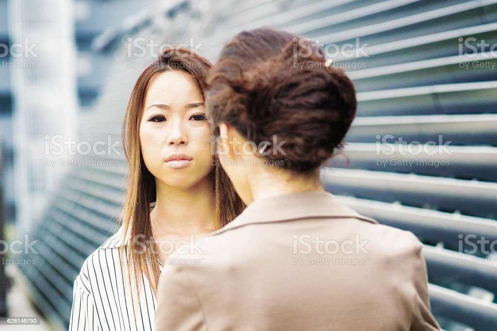 Serious young Japanese woman being scolded by her female boss stock photo