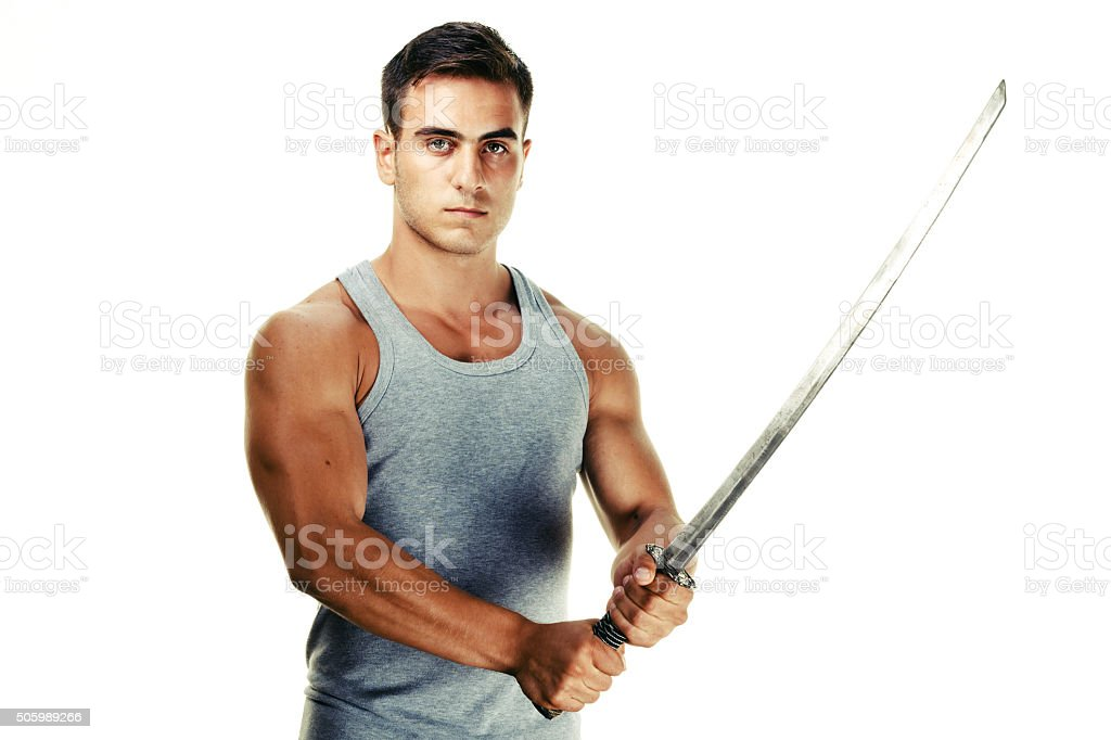 Serious young man and sword stock photo