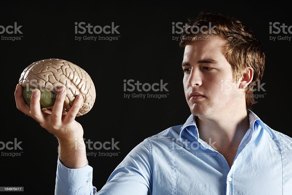Serious young man holds anatomical model of a human brain royalty-free stock photo