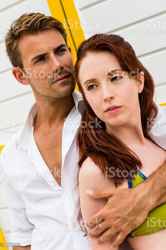 Serious young man hugging young woman stock photo