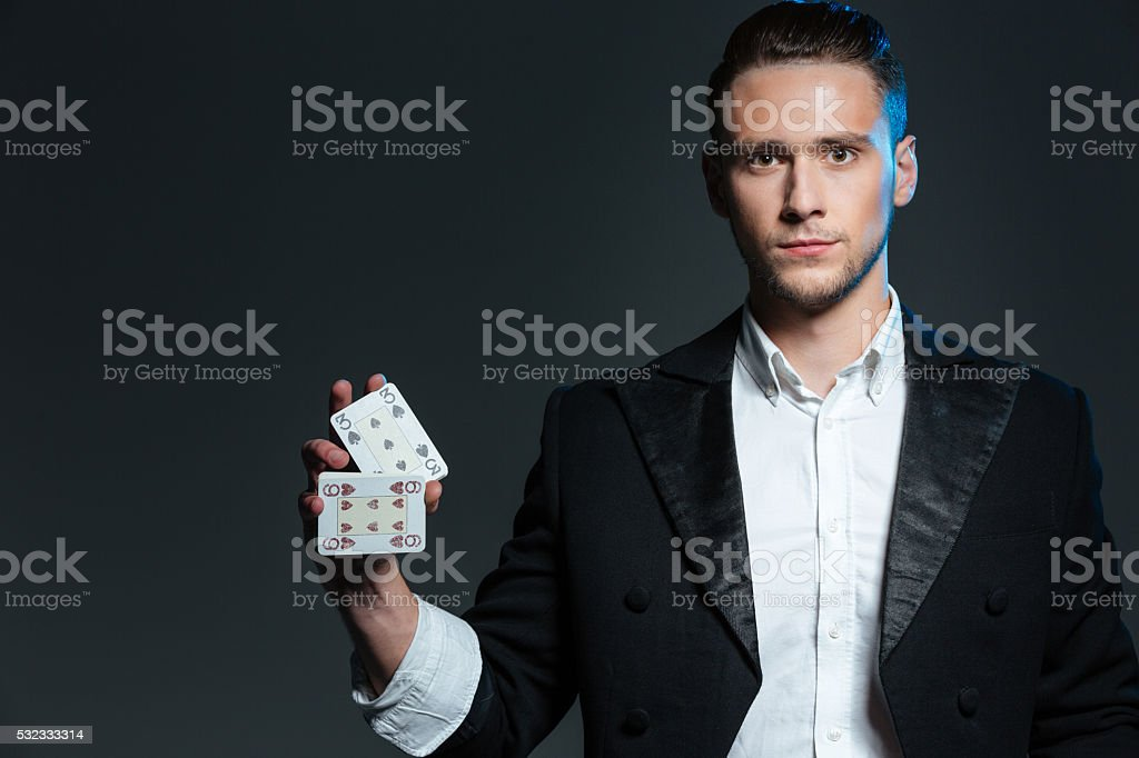 Serious young man magician standing and holding two playing cards stock photo