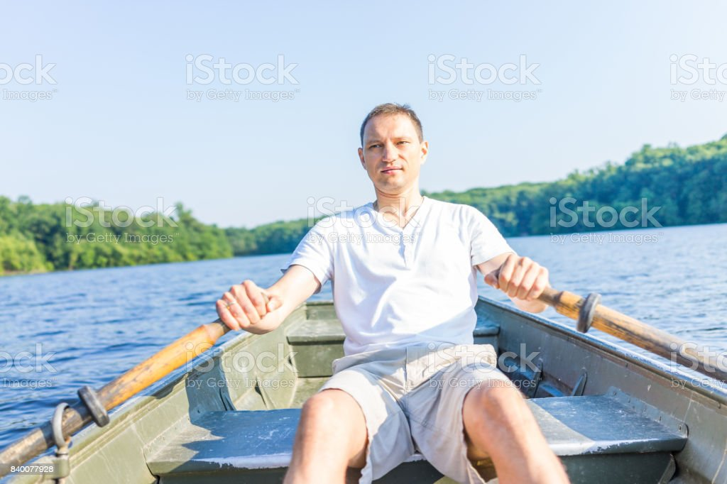 Serious young man rowing boat on lake in Virginia during summer in white shirt stock photo