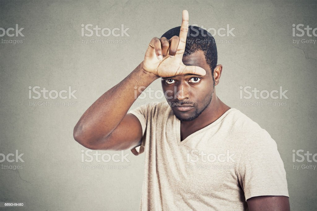serious young man showing loser sign on forehead stock photo