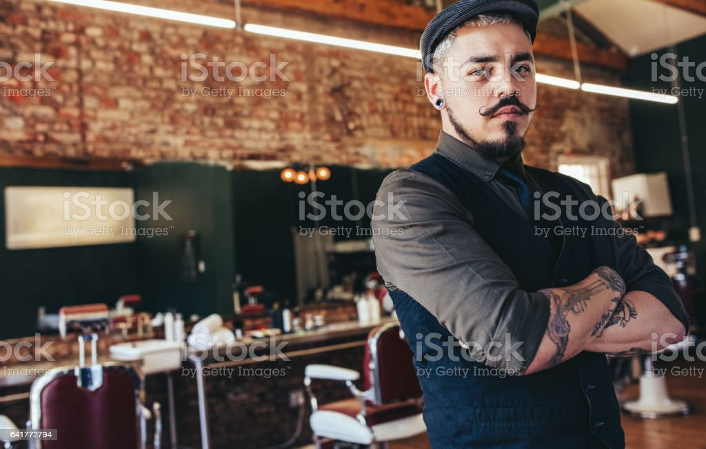 Serious young man standing at barber shop stock photo