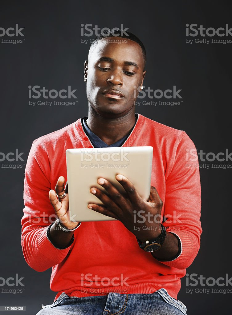 Serious young man taps away at digital tablet touch screen stock photo
