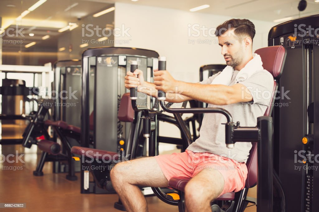 Serious young man training on weight machine stock photo