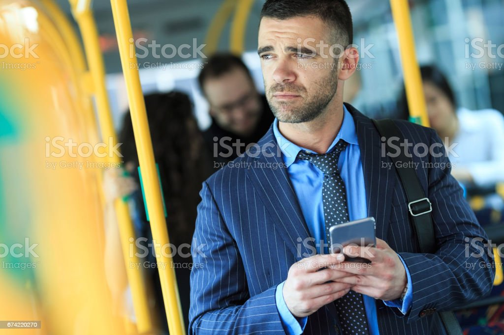 Serious young man traveling and using smart phone stock photo