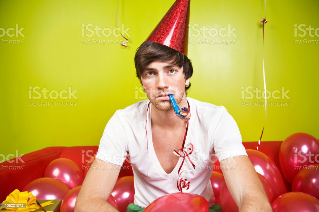 Serious Young Man Wearing Party Hat, Blowing Horn with Balloons stock photo