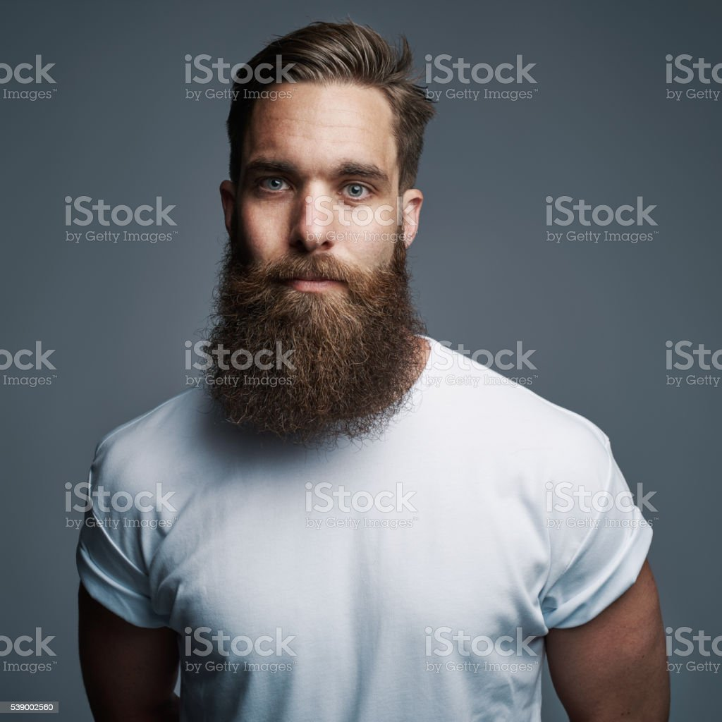 Serious young muscular man with large fuzzy beard stock photo