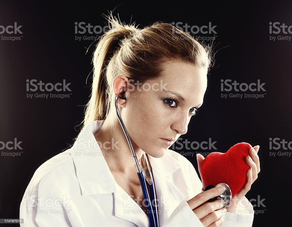 Serious young woman doctor checks Valentine heart with stethoscope royalty-free stock photo