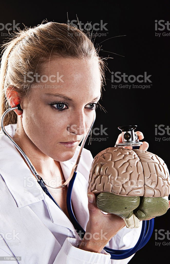 Serious young woman doctor examining model brain with stethoscope stock photo
