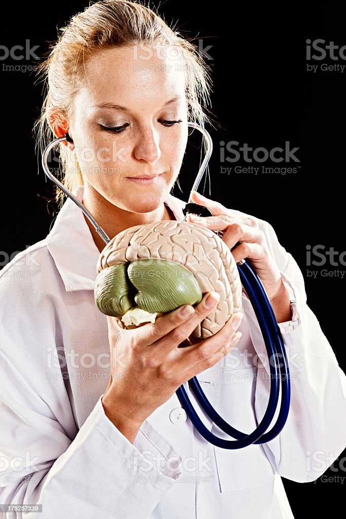 Serious young woman doctor listens to model brain with stethoscope stock photo