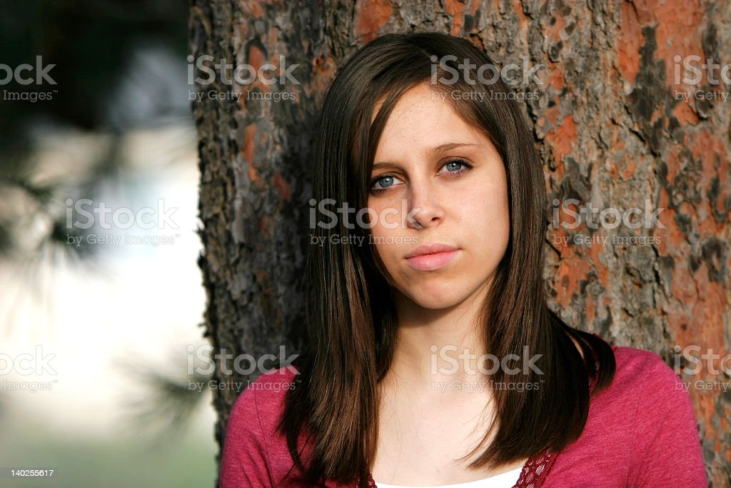 Serious young woman leaning against tree  royalty-free stock photo