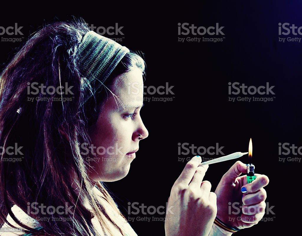 Serious young woman lighting marijuana joint stock photo