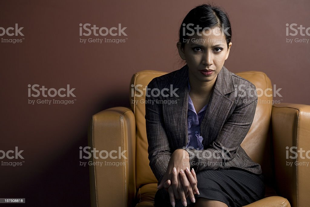 Serious Young Woman on a Sofa Chair royalty-free stock photo