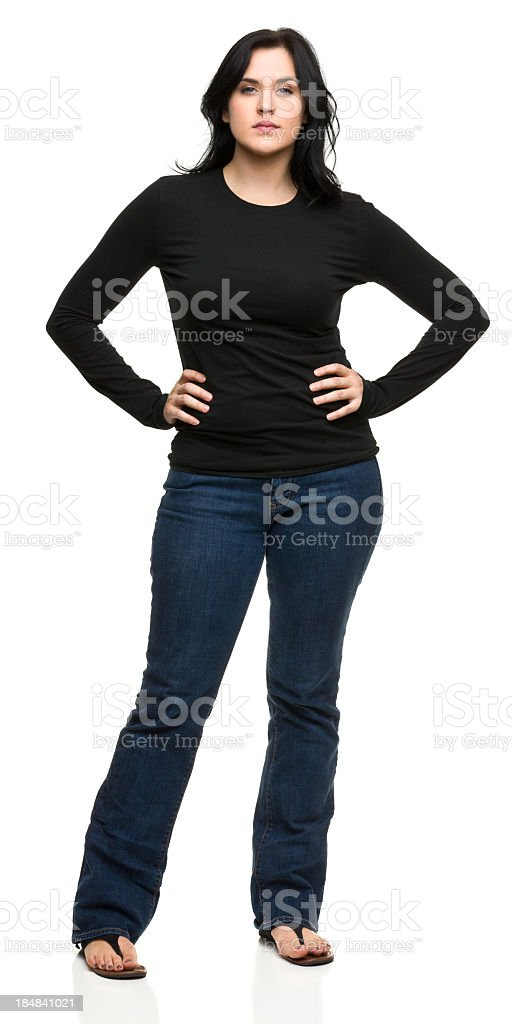 Serious Young Woman Standing With Hands on Hips stock photo