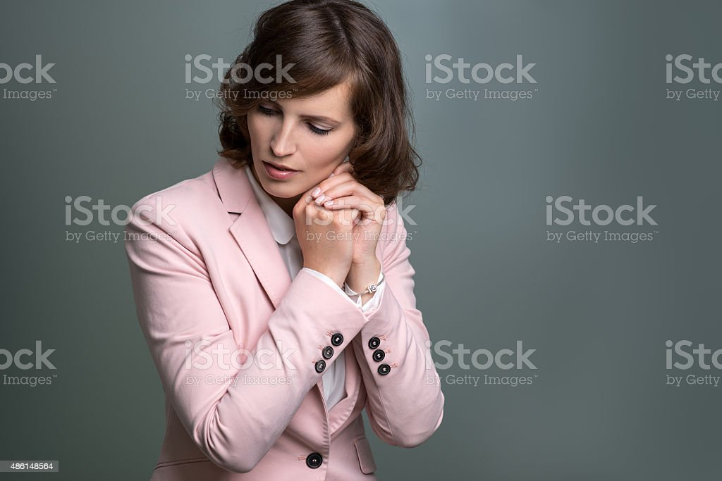 Serious young woman with hands clasped in prayer stock photo