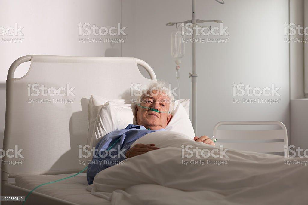 Seriously ill senior man stock photo